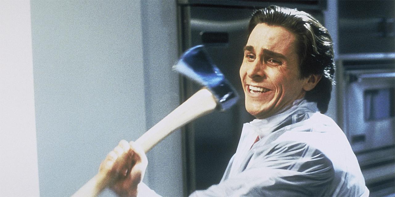 Christian Bale als Patrick Bateman lacht und holt mit der Axt in seinen Händen aus