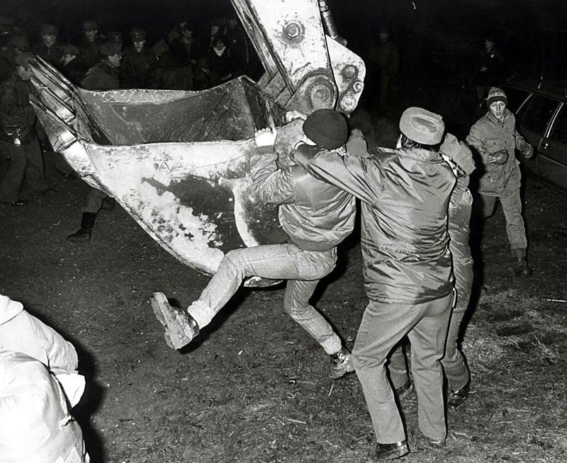 Besetzung der Hainburger Au 1984: Ein Mensch hängt sich an einen Bagger, zwei andere versuchen ihn loszureißen