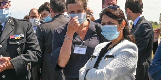 Britain's Home Secretary Priti Patel (C) and French Interior Minister Gerald Darmanin (R), wearing face masks, look at French police equipment during their visit in Calais on July 12, 2020.