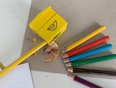 Spitzer mit Post Logo und Buntstifte