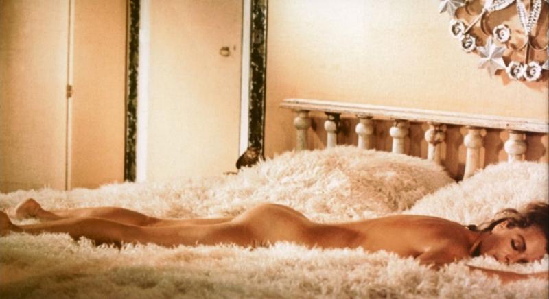 Romy Schneider liegt nackt auf einem Bett