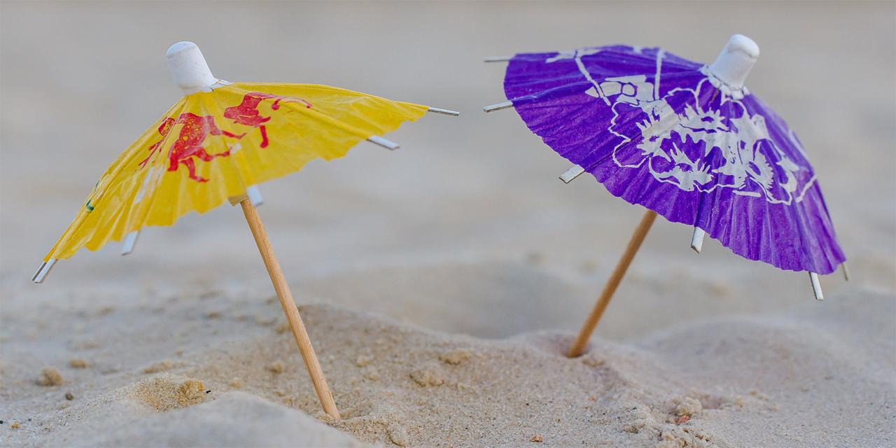 zwei Papierschirmchen stehen im Sand am Strand