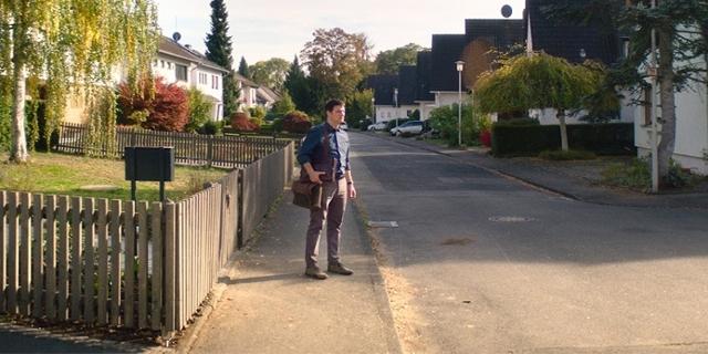"""Mišel Matičević geht eine Straße mit Einfamilienhäusern entlang. Filmszene aus """"Exil"""" von Visar Morina."""