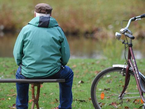 Ein älterer Man sitzt alleine auf einer Bank, daneben steht ein Fahrrad