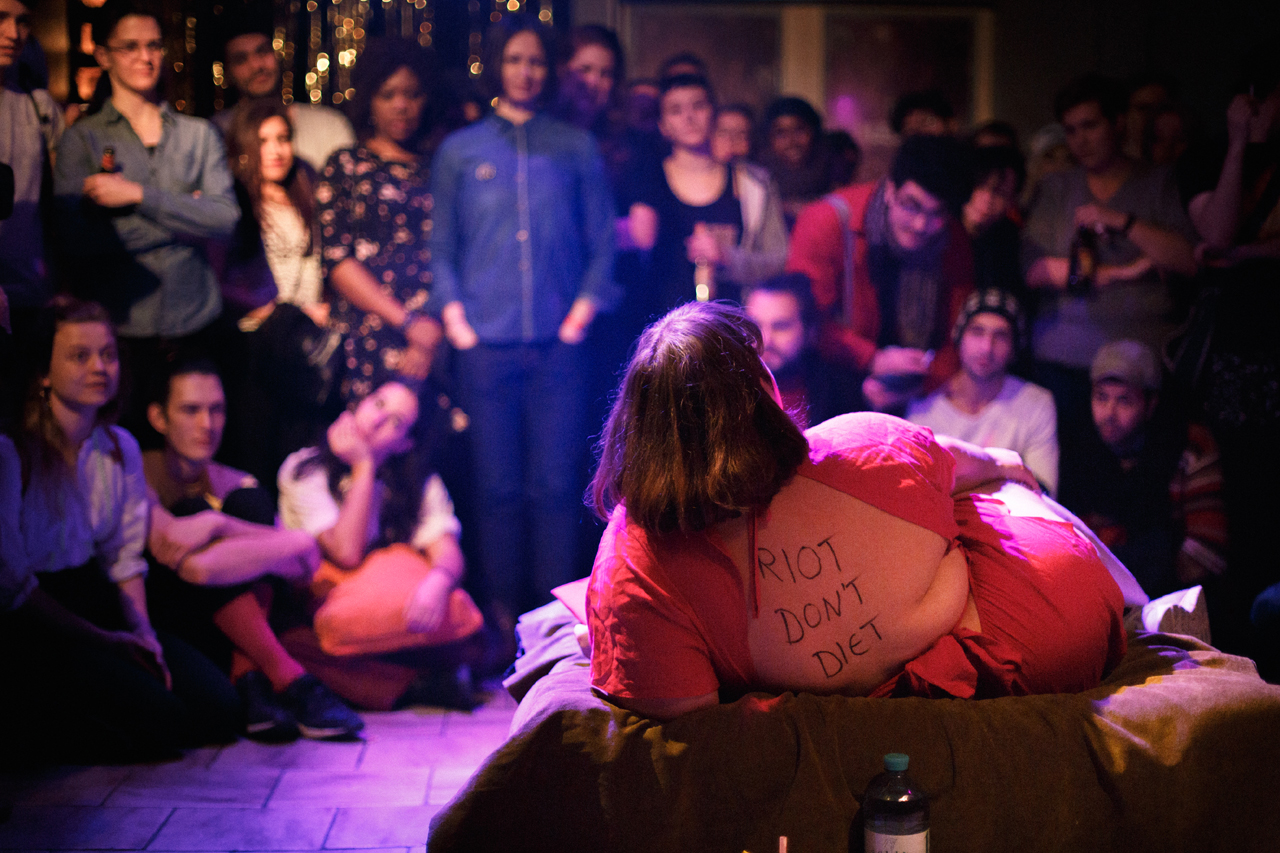 """Julischka Stengele liegt auf einer Bühne vor Publikum, auf ihrem Rücken steht """"Riot not diet"""""""