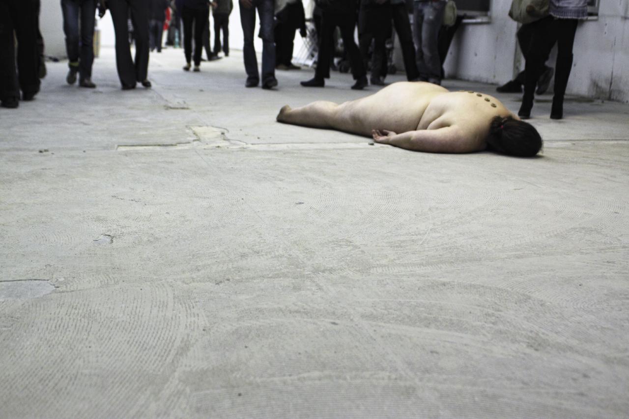 Julischka Stengele liegt auf dem Boden einer Galerie, rundherum stehen Menschen