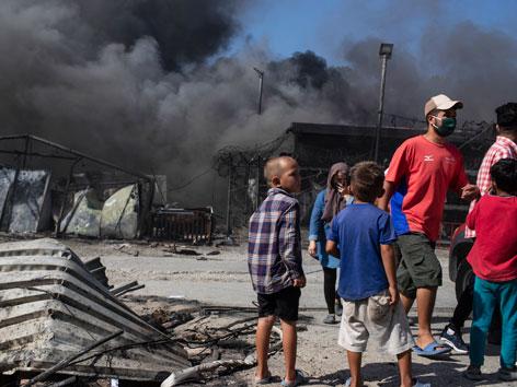EIn Mann und Kinder neben rauchenden Überresten des Flüchtlingslagers Moria
