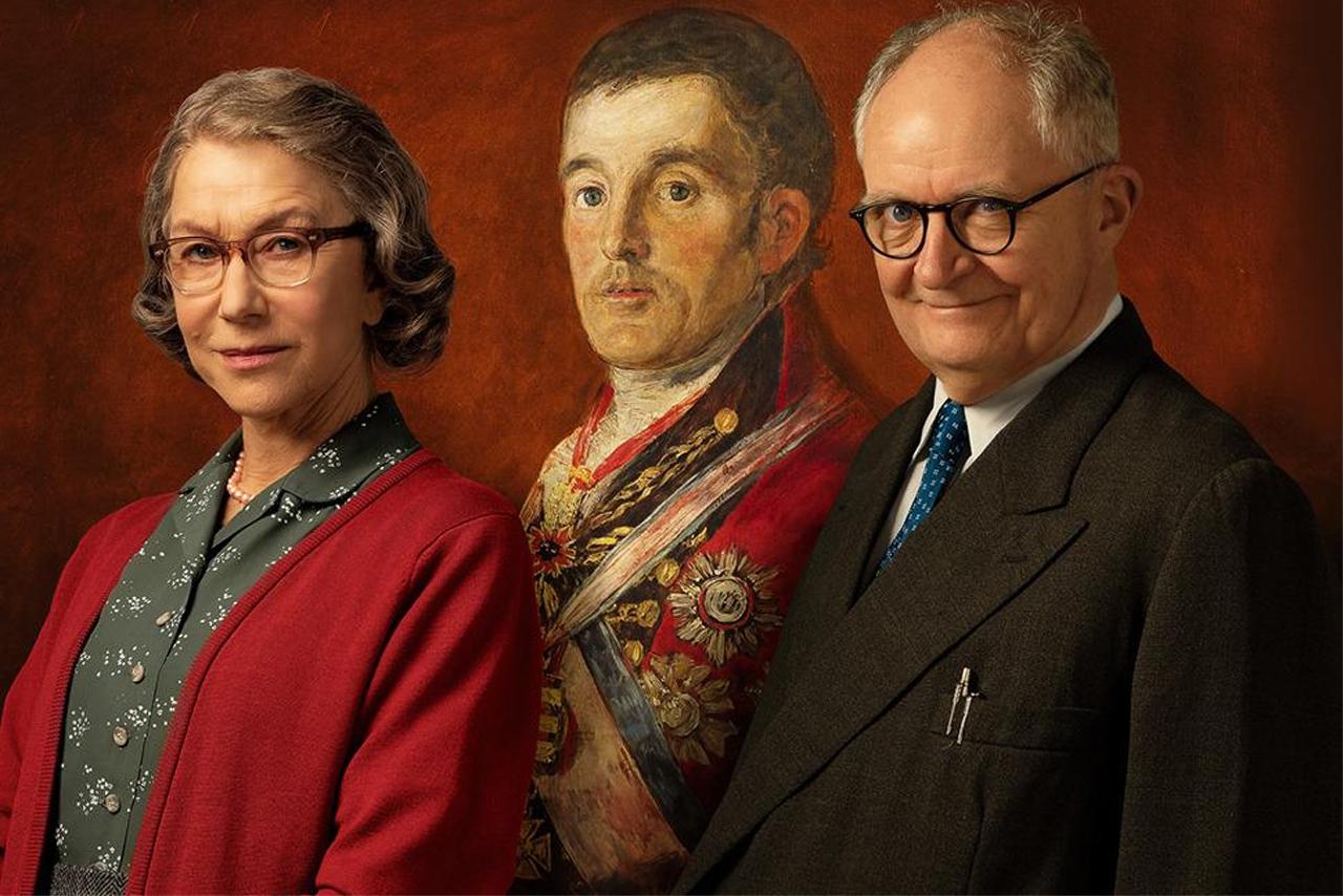 Filmstill: Eine Frau und ein Mann posieren vor einem Gemälde