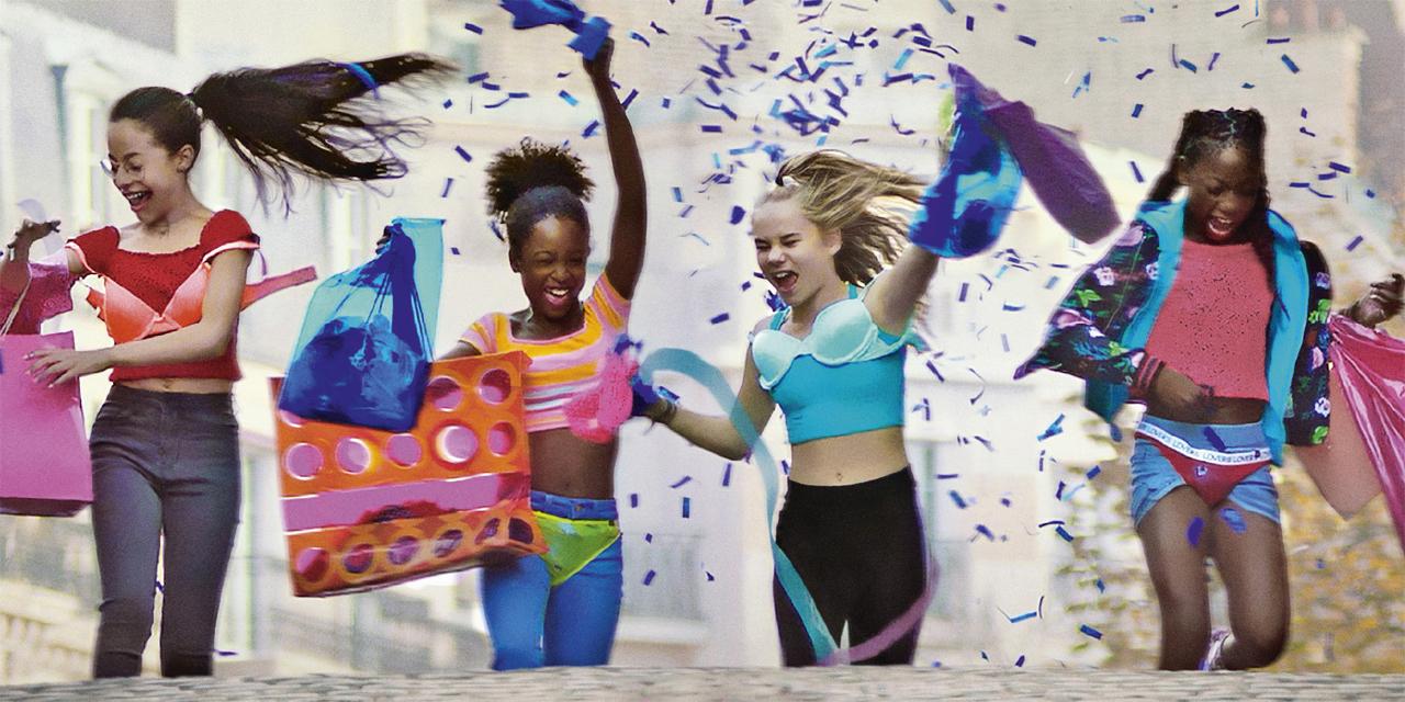 Vier Mädchen ziehen feiernd durch eine Straße, sie tragen BHs und Slips über ihren Kleidern
