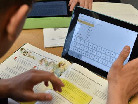 Ein Schüler mit Laptop und Schulbuch