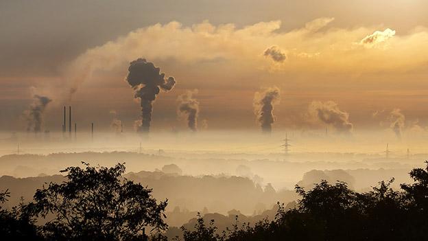 Rauch steigt aus Fabriksschornsteinen auf