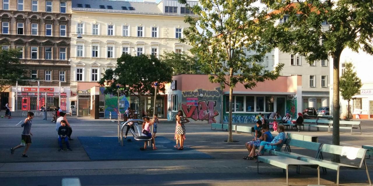 Volkertplatz: Menschen sitzen auf Bänken