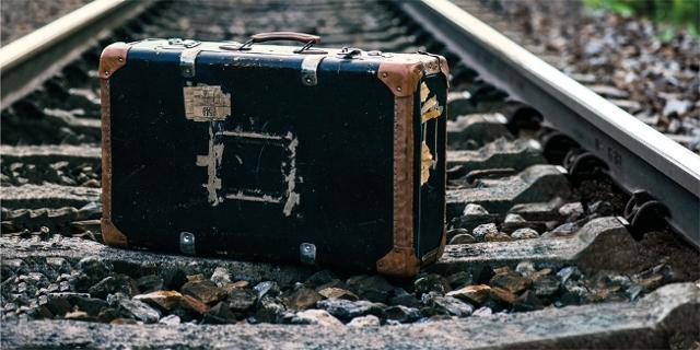 Ein Koffer steht auf Eisenbahngleisen