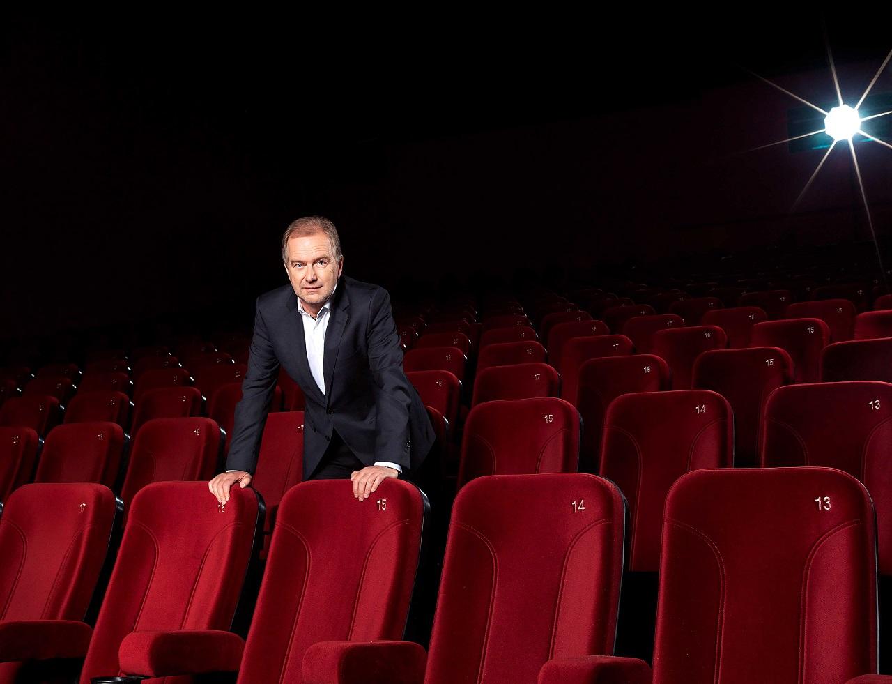 Christian Langhammer, der Geschäftsführer von Cineplexx, steht in einem Kinosaal zwischen den Sitzreihen.