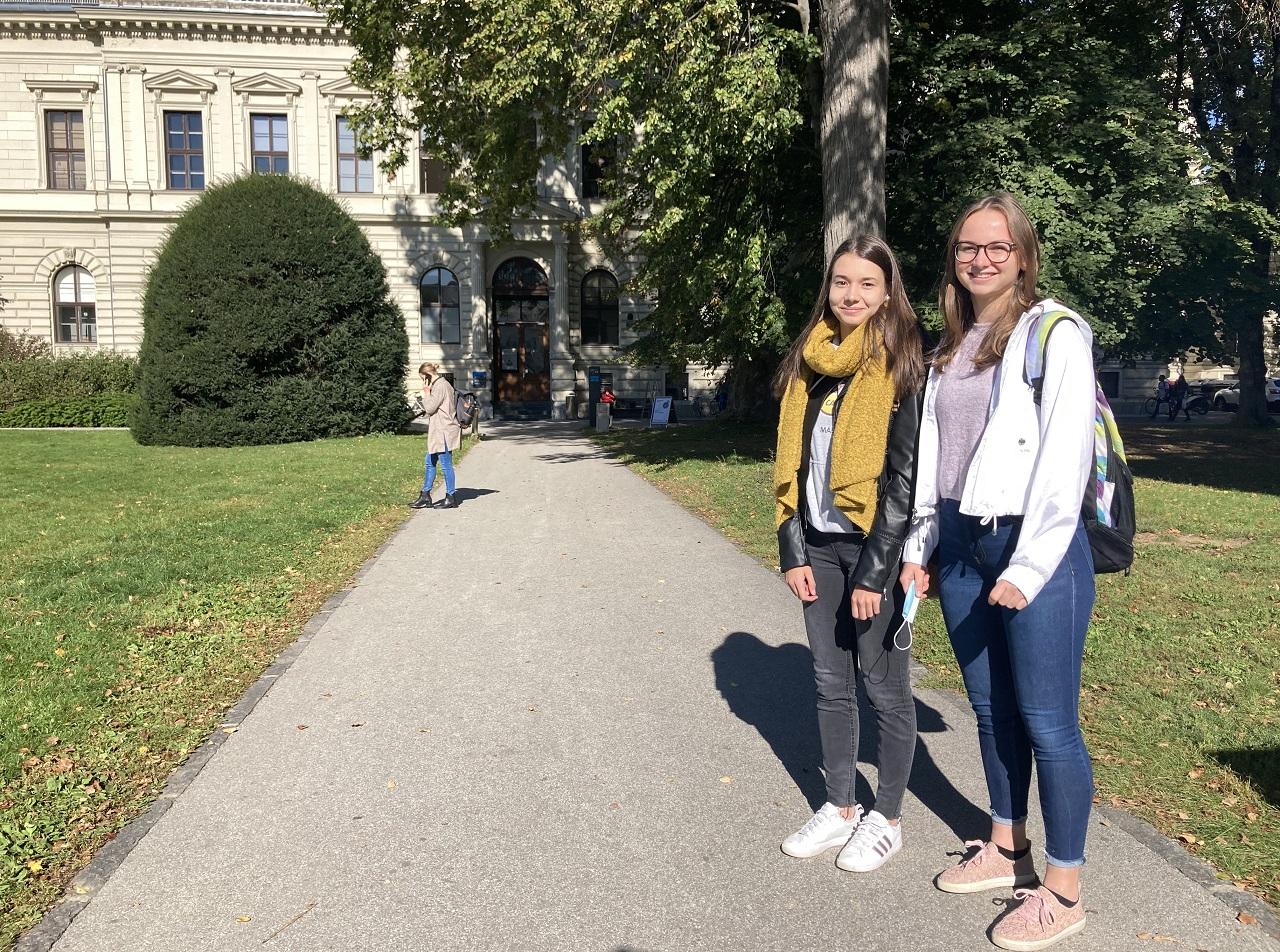 Zwei junge Frauen stehen am Universitätsgelände.