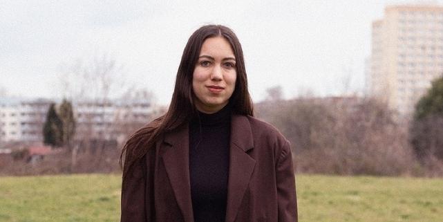 Ronya Othmann lächelt, sie steht auf einem freien Feld und trägt einen Anzug.