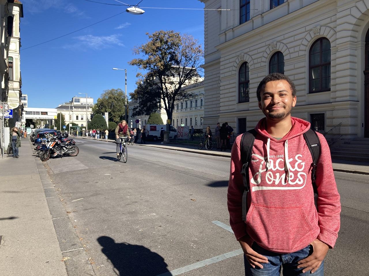 Ein junger Mann steht nahe der Karl-Franzens-Universität und freut sich auf das erste Semester als Student.