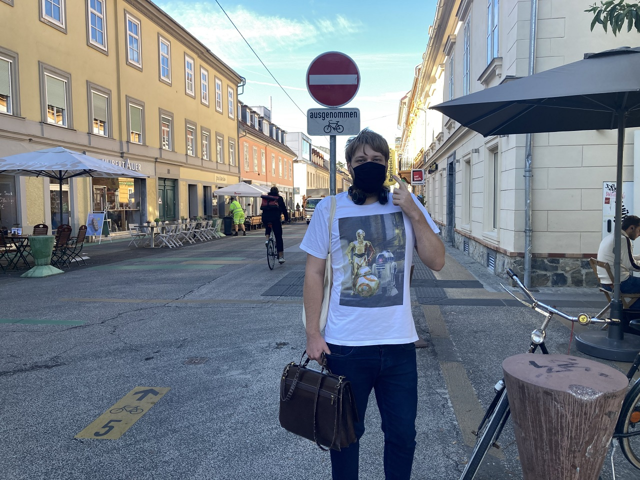 Ein  Student trägt einen Mund-Nasen-Schutz, auf den er mit einer Hand zeigt, und steht in der Grazer Zinzendorfgasse nahe der Uni.