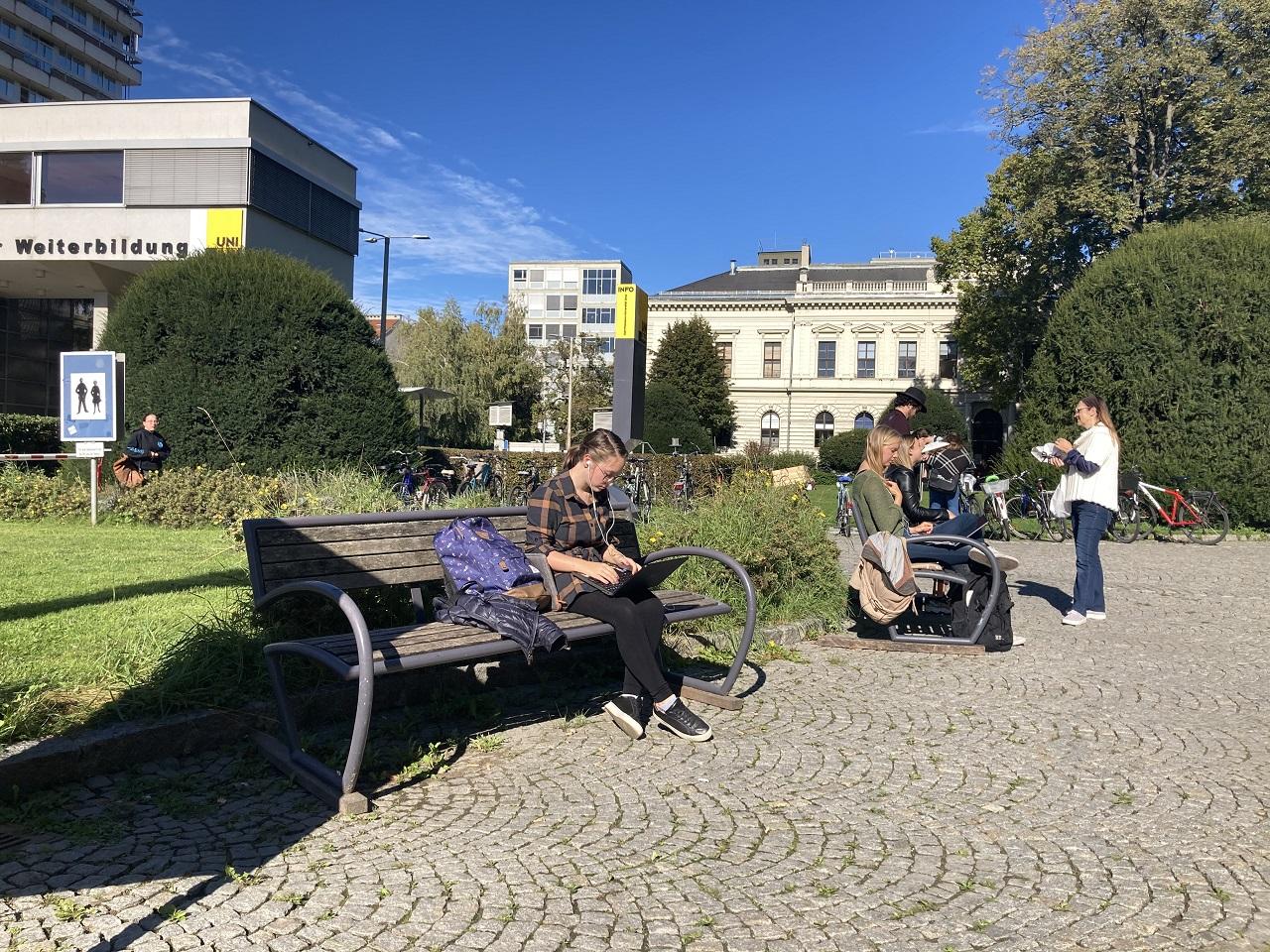 Studierende sitzen auf Bänken vor der Karl-Franzens-Universität und verfolgen ihre Vorlesungen über die Laptops im Stream.