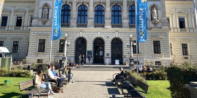 Das Hauptgebäude der Karl-Franzens-Universität in Graz, davor sitzen Studiererende auf den Bänken und unterhalten sich.