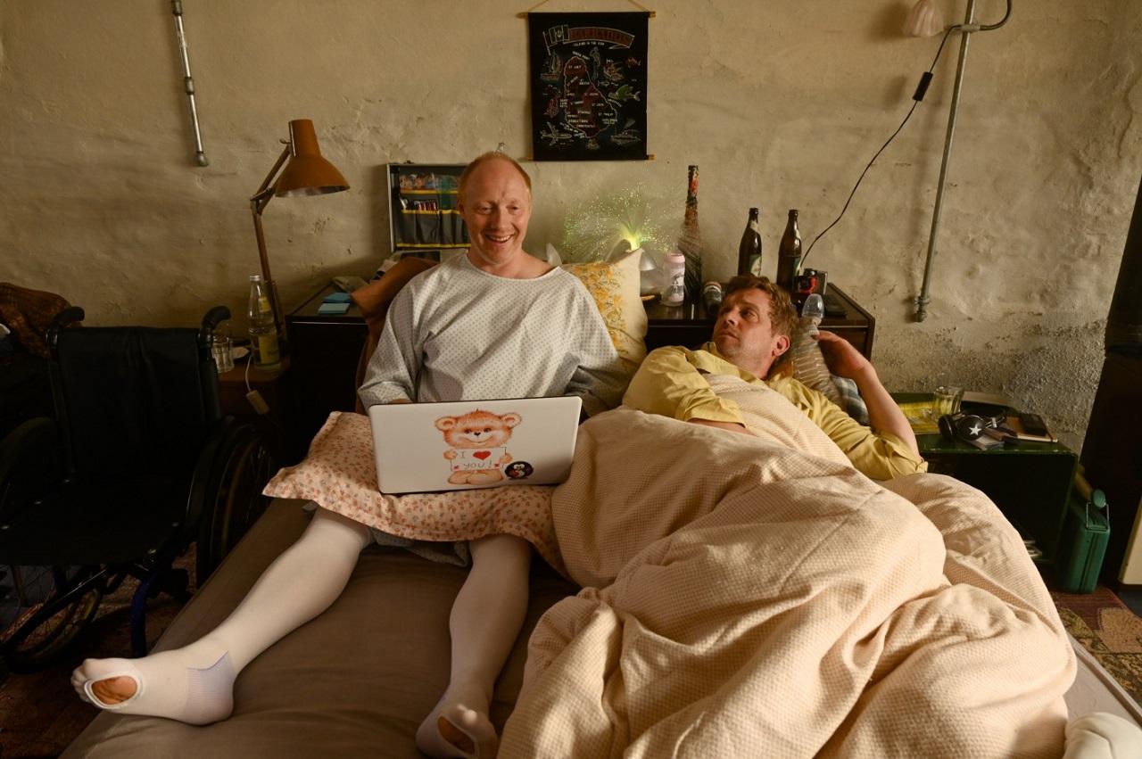 """Sebastian Bezzel und Simon Schwarz sitzen an einem Tisch und schauen auf einen Laptop. Filmstill aus """"Kaiserschmarrndrama"""""""