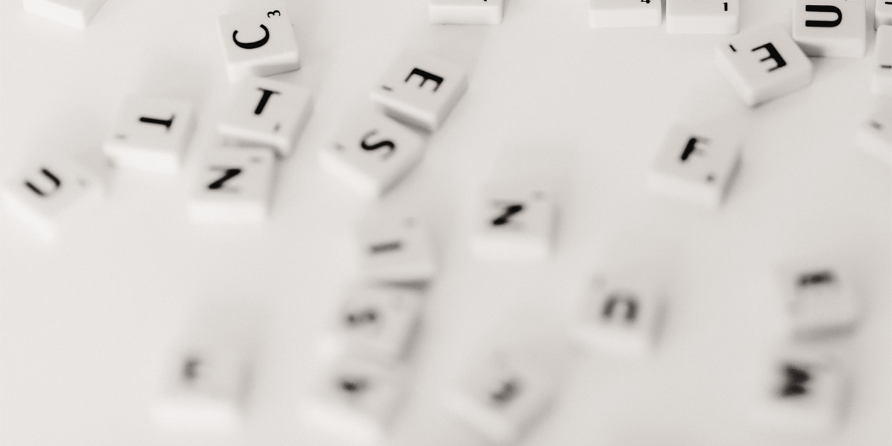 Scrabble Buchstaben, leicht verschwommen und durcheinander auf weißem Hintergrund