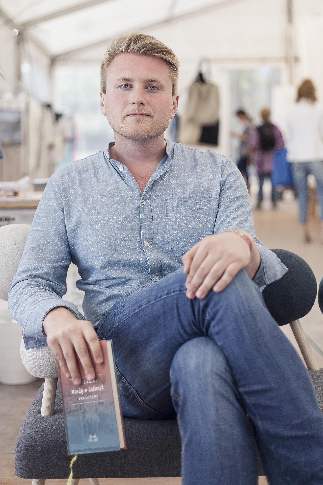 Der Autor Peter Balko trägt ein Hemd und hält ein Buch in der Hand
