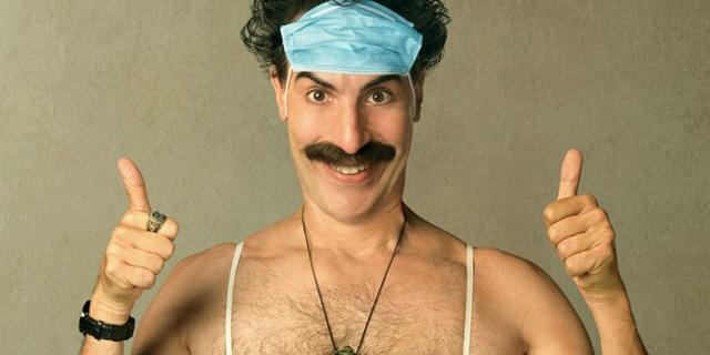 Borat mit Maske auf der Stirn und Daumen hoch