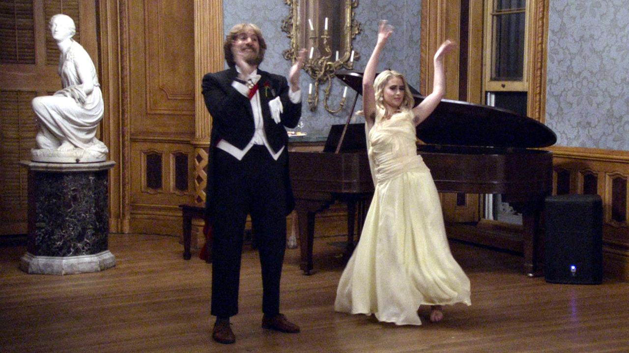 Borat und seine Tochter in Abendgarderobe vor einem Flügel. Sie klatschen und tanzen.