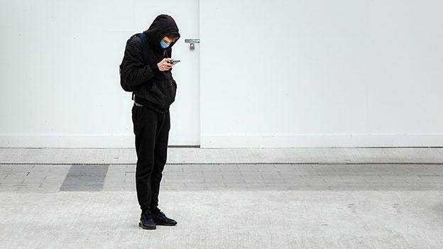 Mann mit Maske vor einer verschlossenen Tür