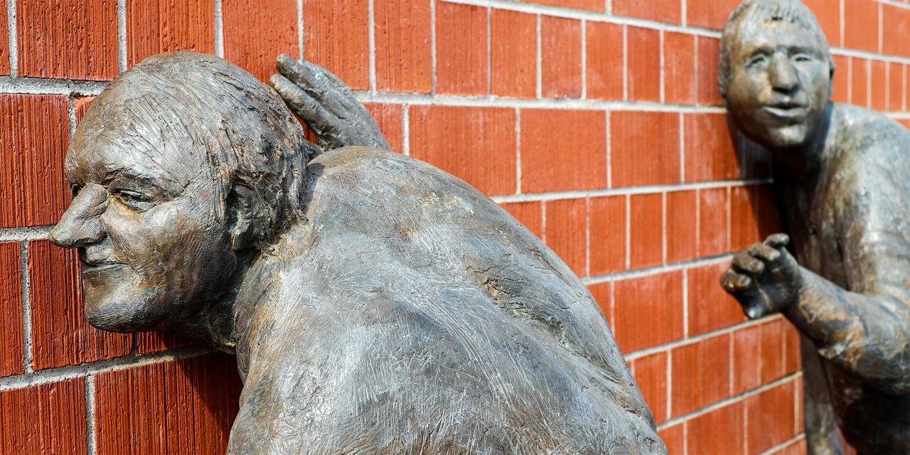 Bronzeskulpturen: Menschen, die an einer Mauer lauschen