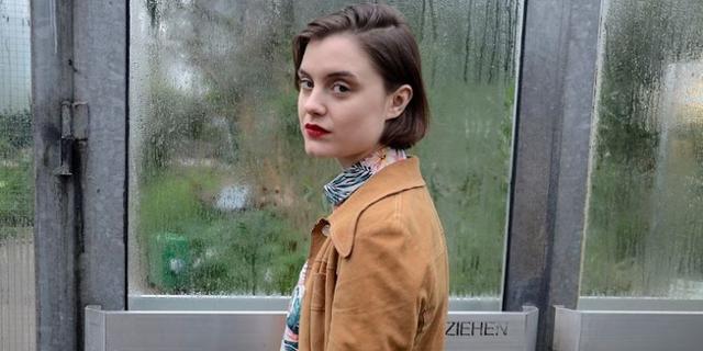 Sophia Kennedy vor einem Fenster schaut über die Schulter nach hinten
