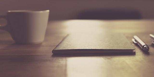 Kaffee und Schreibutensilien am Schreibtisch