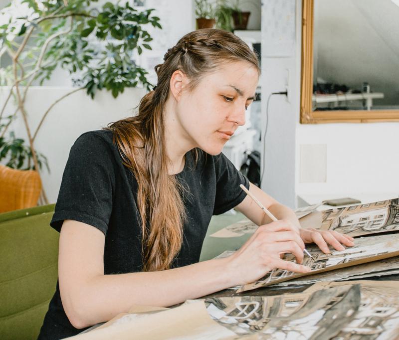 Paulina Stulin beim Zeichnen am Tisch