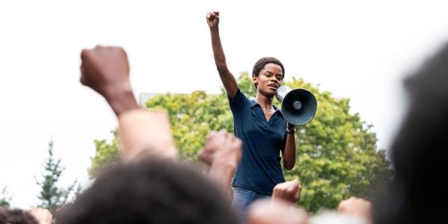 Demonstration: Eine Sprecherin mit Megaphon