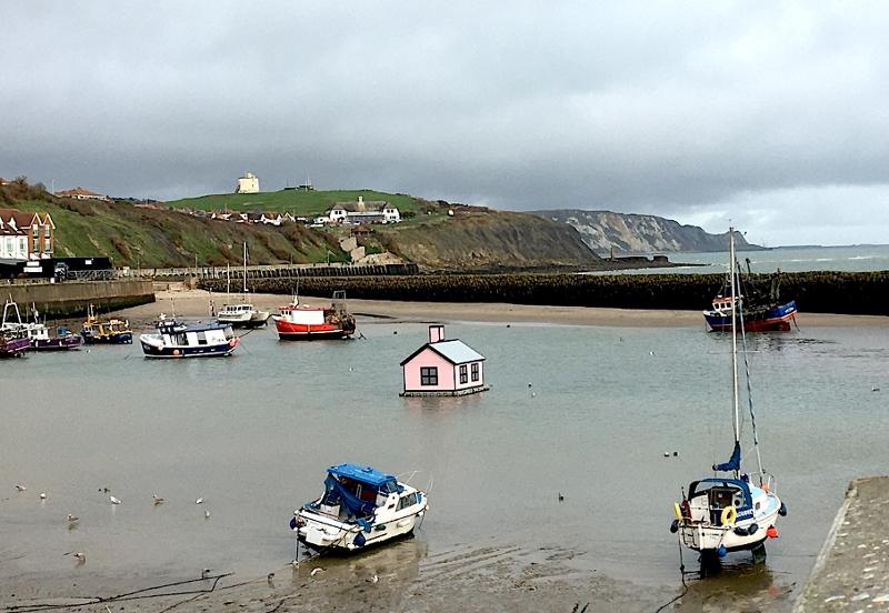 Schwimmendes rosa Haus und Boote im Meer vor Folkestone