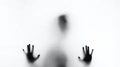 Silhouette eines Mannes hinter einer Scheibe