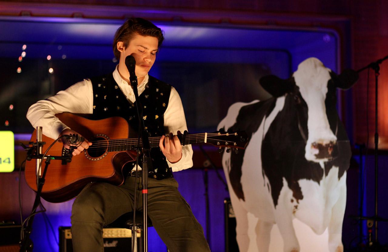 Marcus Hinterberger in Tracht mit Gitarre vor einem Kuh-Aufsteller aus Karton
