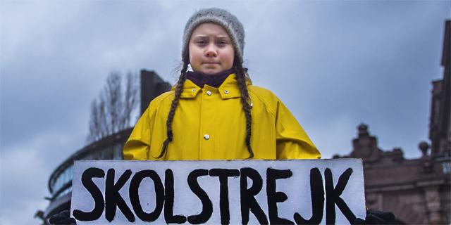 """Greta Thunberg Ende November 2018 vor dem schwedischen Parlament. Sie hält ein Schild mit der Aufschrift: """"Schulstreik fürs Klima"""""""