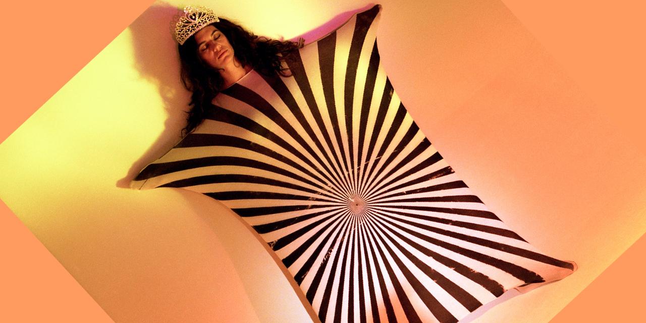 Eine Frau trägt eine Krone und hat die Augen geschlossen. Sie spannt ein Tuch mit schwarz-weißen, in der Mitte zusammenlaufenden Streifen über ihren Körper.