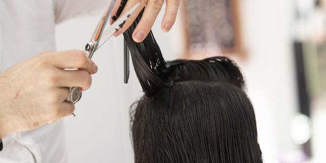 Nahaufnahme beim Frisör: Haare, Hand und Schere