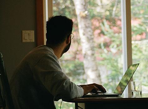 Mann arbeitet am Laptop und schaut aus dem Fenster