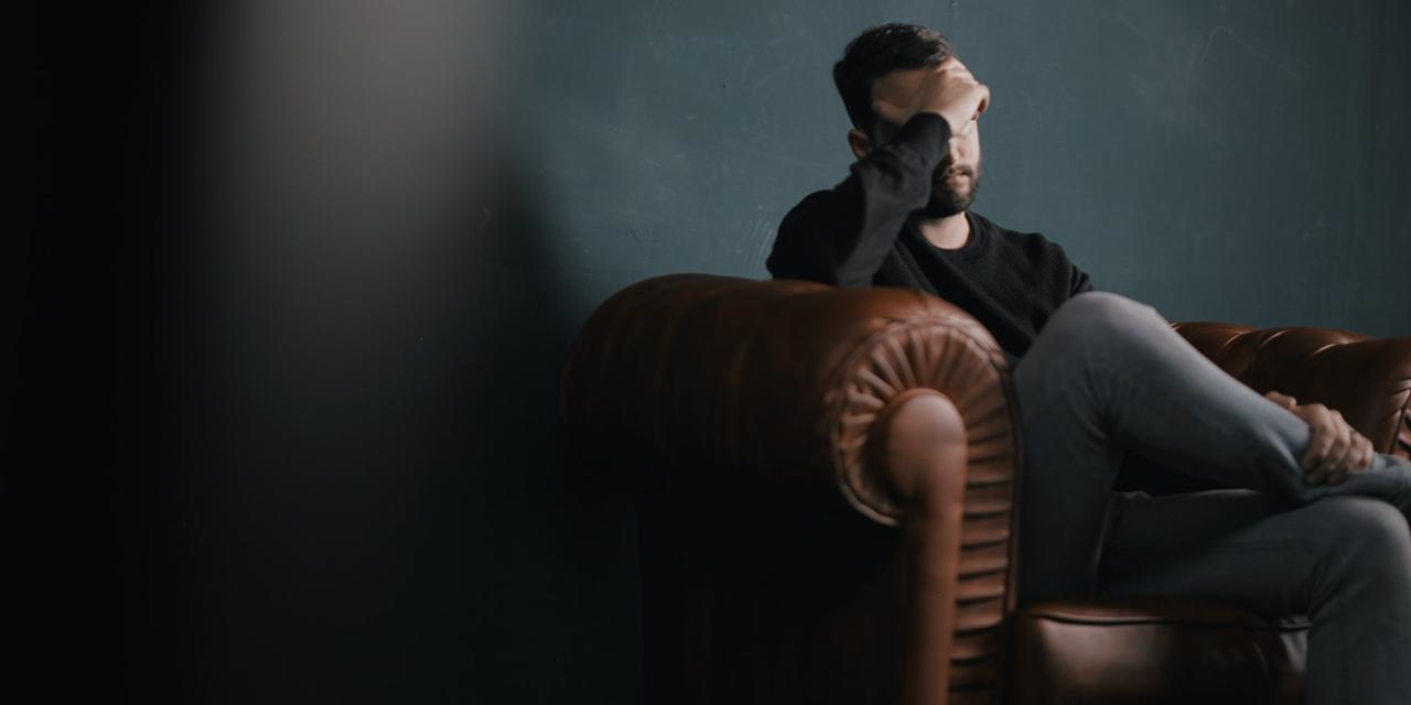 Mann sitzt bei der Psychotherapie