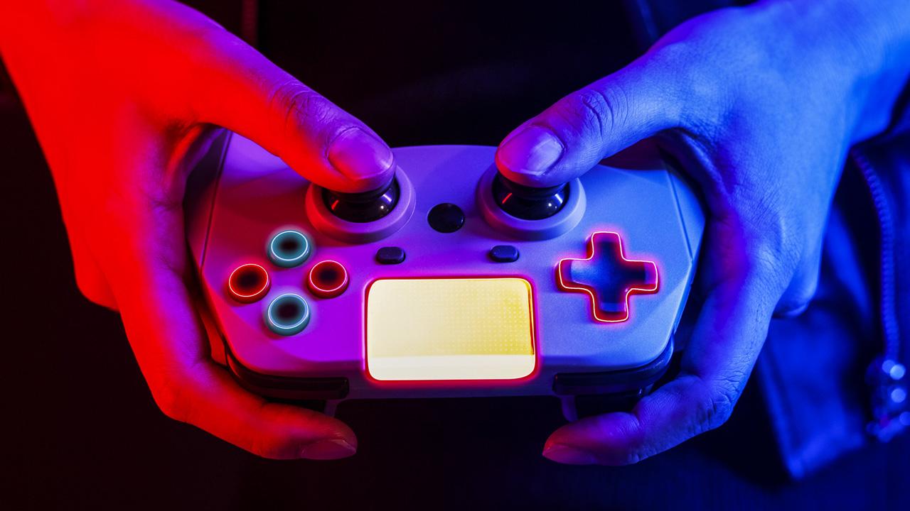 Ein Gamecontroller, der von zwei Händen gehalten wird, in Neon-Ästhetik.