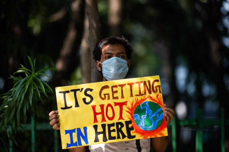 """Teilnehmer einer Fridays for Future Demon in Neu Delhi im September 2020 hält ein Schild mit der Aufschrift: """"It's getting hot in here"""""""