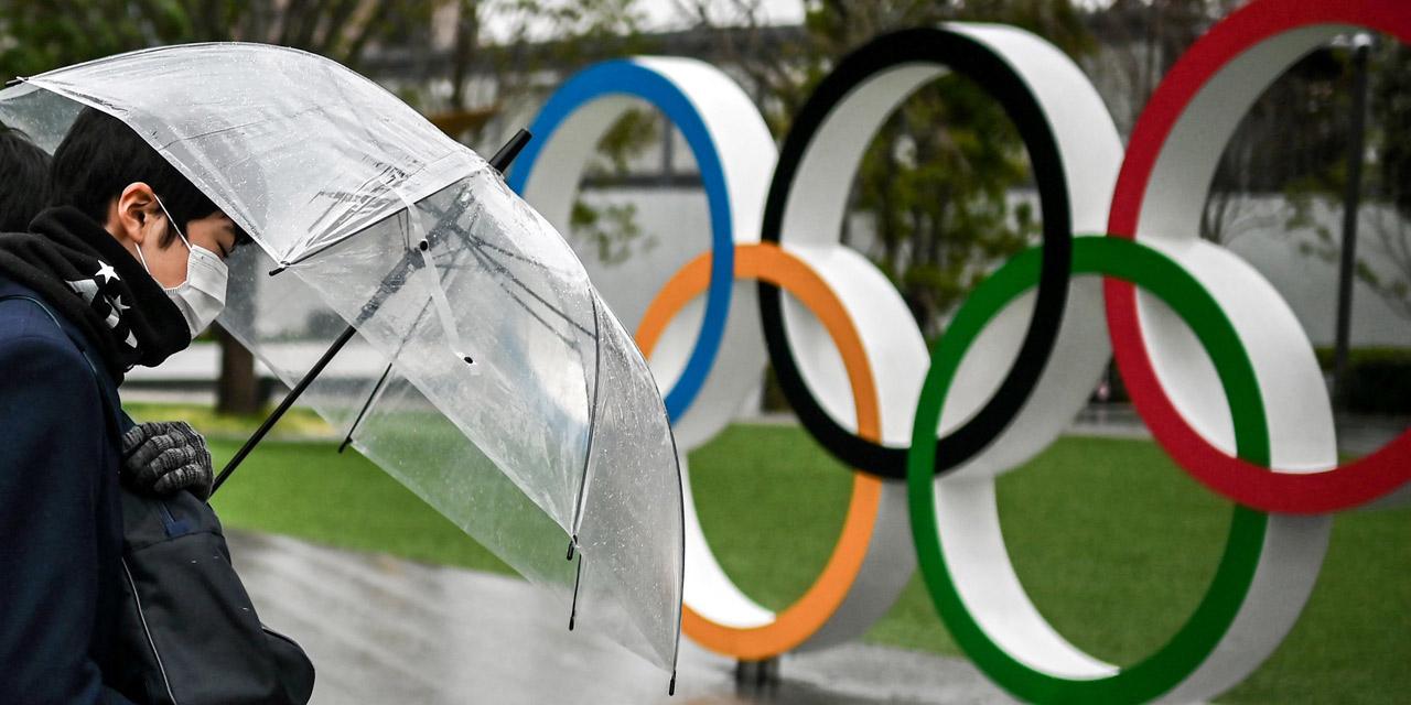 Japaner mit Regenschirm vor den Olympischen Ringen in Tokio