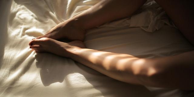 nackte Beine auf einem Bettlaken, Schatten und Sonnenlicht