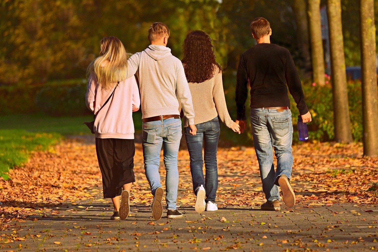 4 Personen gehen in einem Park spazieren