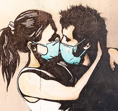 Mann und Frau küssen sich mit Schutzmaske