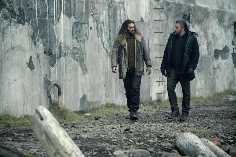 Zwei Männer gehen eine Mauer entlang und reden miteinander